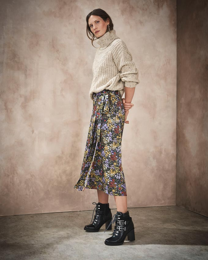 A beige jumper over a flower print skirt paired with black booties. Image via Marks&Spencer.