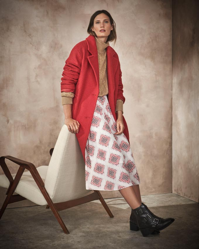 A woman dressed in a red coat, midi skirt, beige top and black ankle boots. Image via Marks&Spencer.