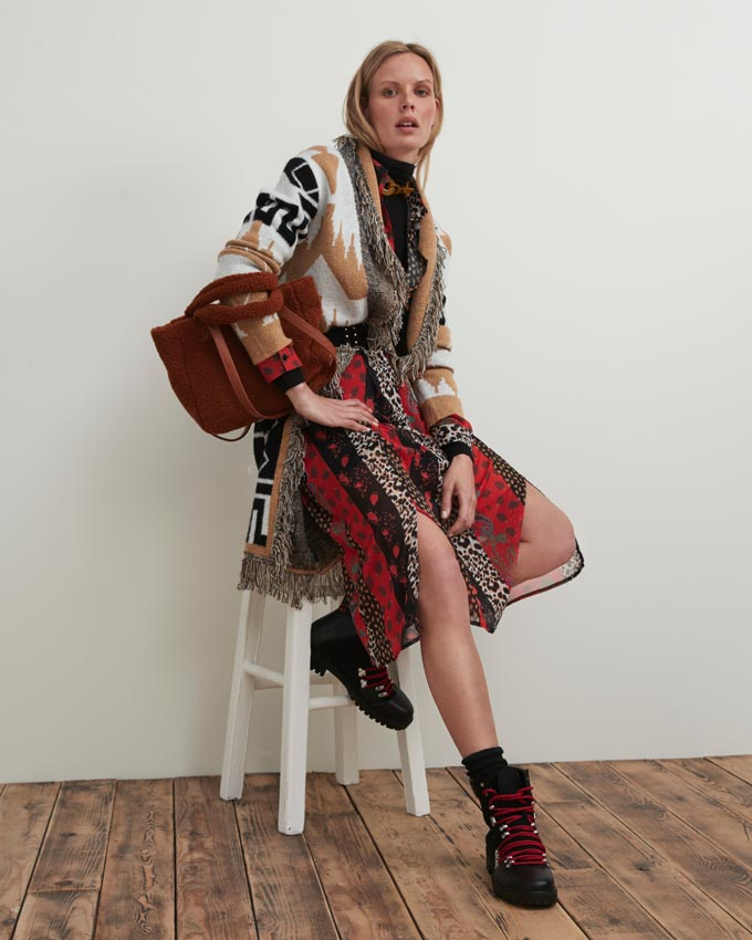 An outfit with a boho flair - a dress under a long patterned knit cardigan paired with hiking boots. Image via Matalan.