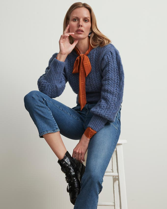 A woman dressed in a casual outfit with denims and jumper wearing combat boots. Image via Matalan.