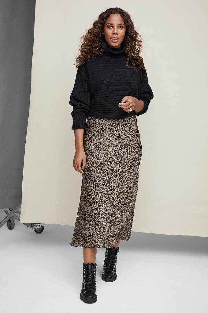 A woman dressed with a black jumper, a midi leopard print skirt. Image via New Look.