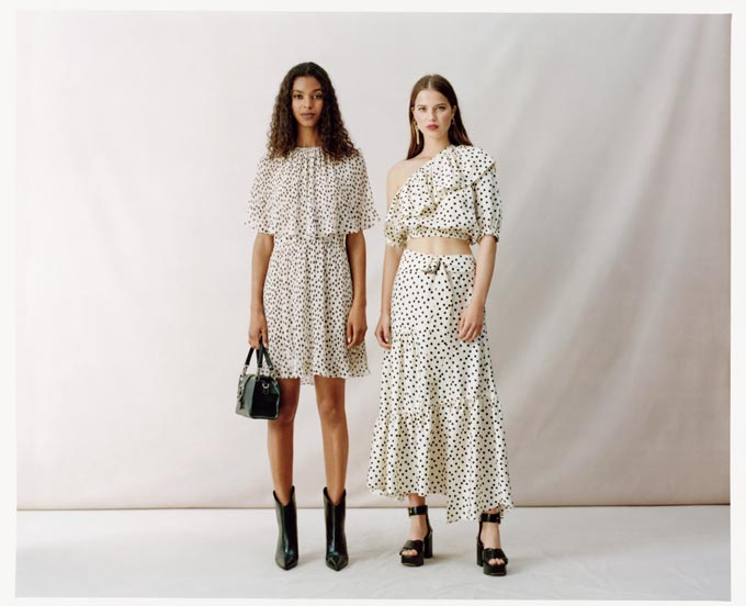 Two women in polka dot outfits one wearing western styled boots, the other sandals. Image via Topshop.