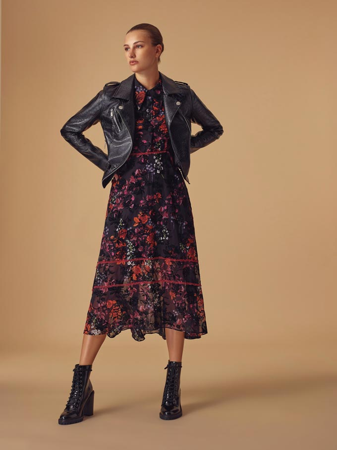 Winter outfits lookbook: A print winter dress paired with a black biker's jacket and ankle boots. Image via Very.co.uk.