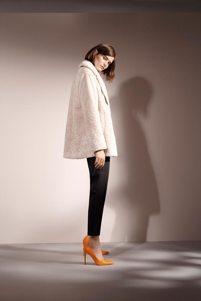 A woman in an off-white faux fur coat, black pants and orange pumps. Image via Wallis.