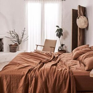 A bright Scandi-boho chic bedroom with rusty hue bedding, looking out of this world. Image via IN BED. Photo by Terence Chin Photography.
