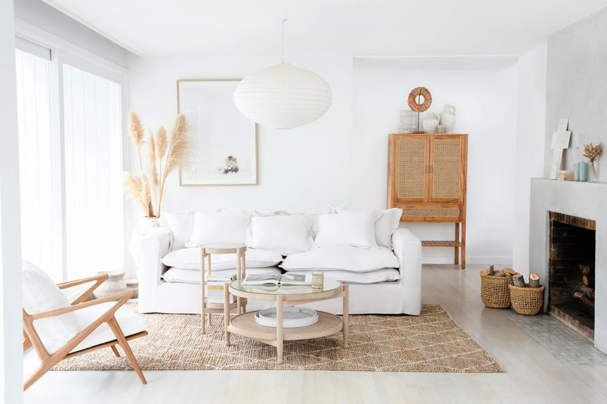 A bright white Scandi boho living room with a neutral color palette and elements like cane and rattan. Image via OZ Design Furniture.