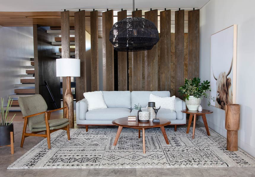 A chic Scandi-boho inspired living room with a soft grey sofa, a large black rattan pendant light, a patterned in neutral colors area and lots of wooden surfaces. Image via OZ Design Furniture.