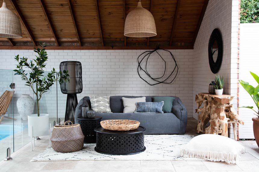 An elegant Scandi-boho setup with a blue sofa and a rattan pendant light hanging from a wooden sloped roof. Image via OZ Design Furniture.