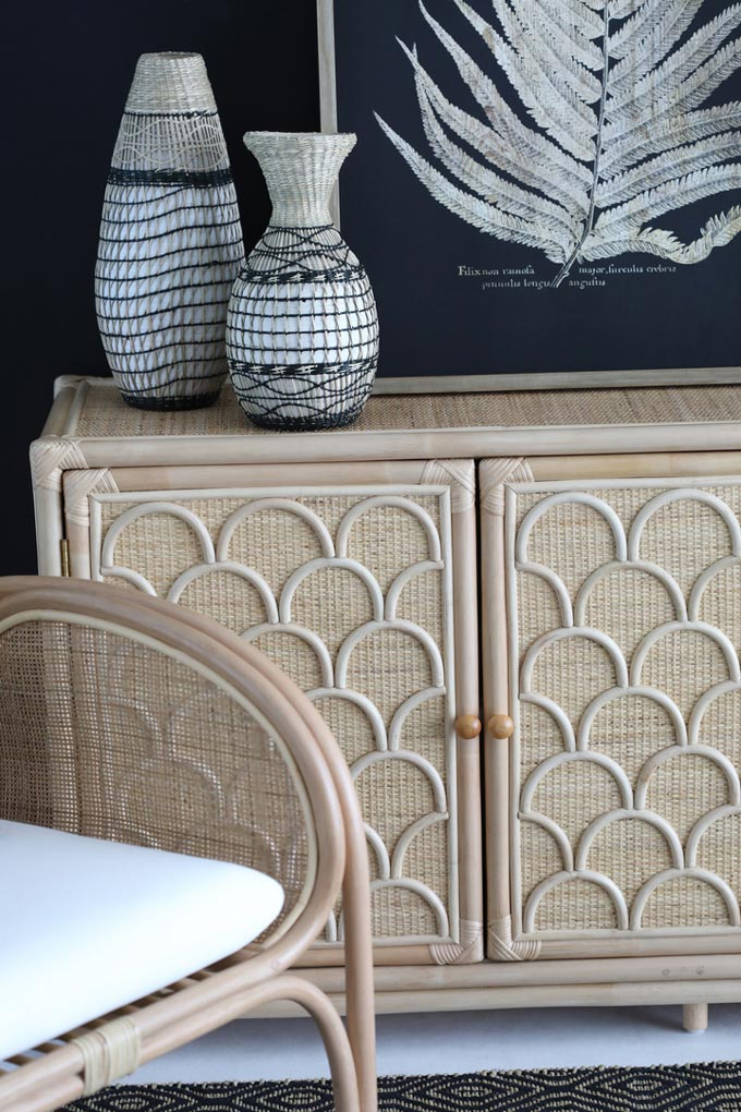 Detail view of a vignette featuring a beautiful credenza made of rattan and cane, decorated with some patterned bases.Alongside is a handmade rattan chair. The navy blue wall color behind helps them pop up. Image via OZ Design Furniture.