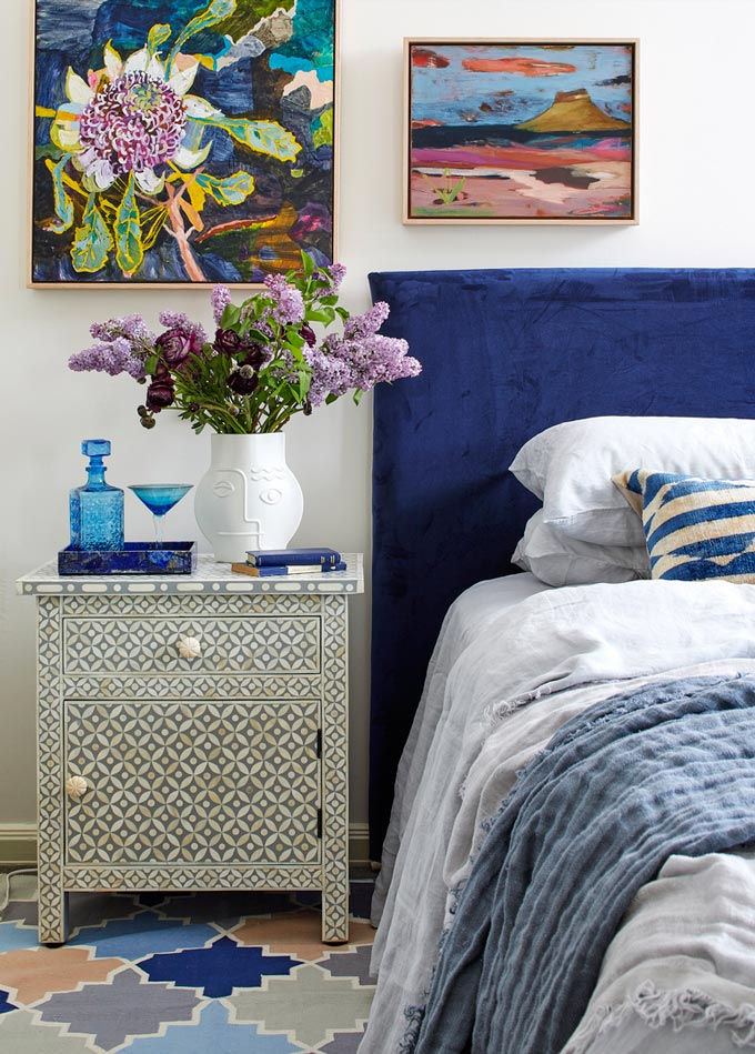 A partial view of a Boho-chic bedroom with a bed's blue headboard and colorful artwork hanging from the wall. Image via Fenton & Fenton by Dave Kulesza.