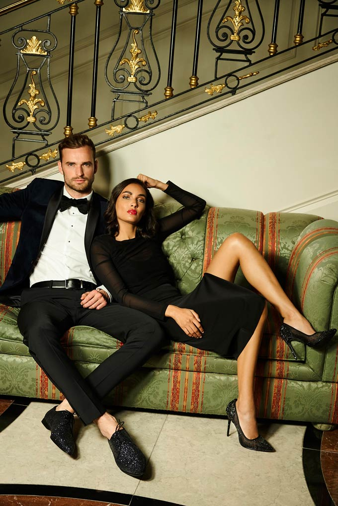 A handsome couple dressed up in holiday outfits. He's wearing a black suite, she's wearing a velvet dress with shears and black glittering high pumps. Image via Dune.