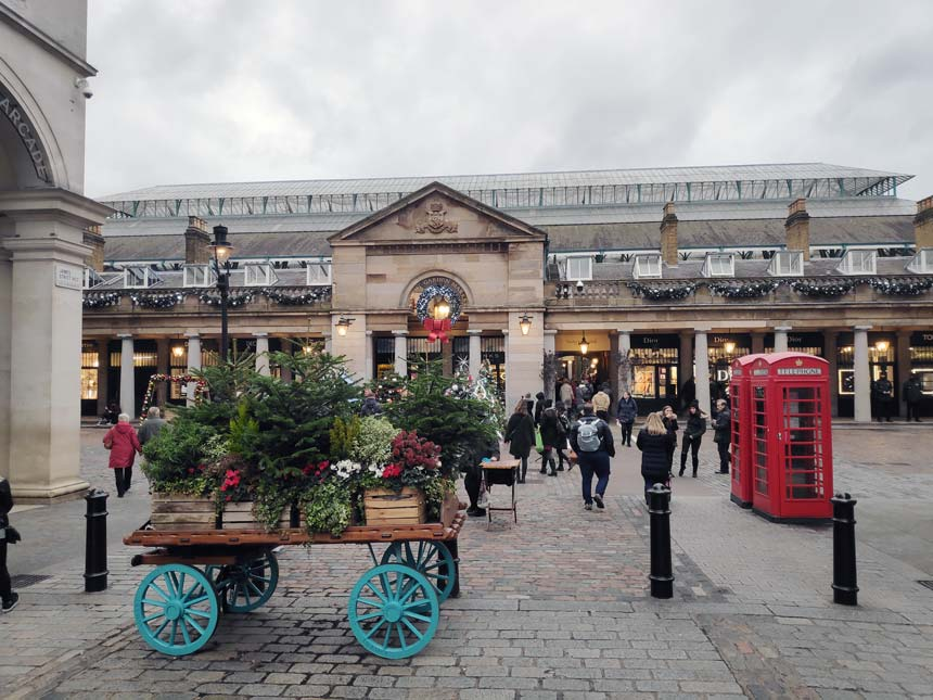 View of the walkway towards Covent Garden's Halls with Christmas decorations around and plenty of walking by people.