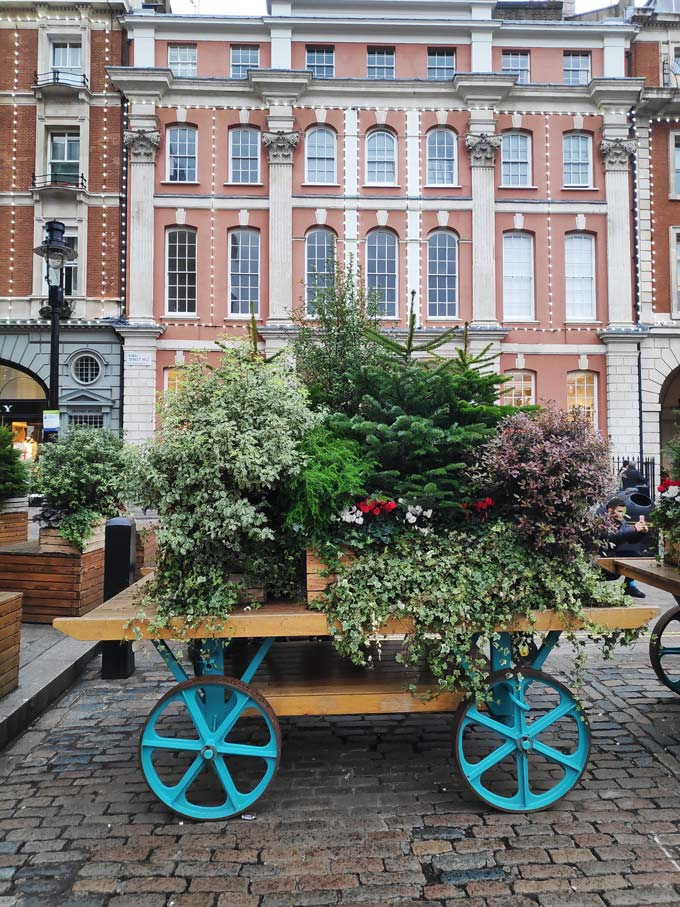 A wheel cart decorated with Christmas trees and plants at Covent Garden's square in London.