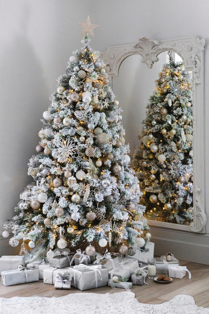 An almost white Christmas tree decorated with white and gold baubles. A real classic option. Image via Amara.