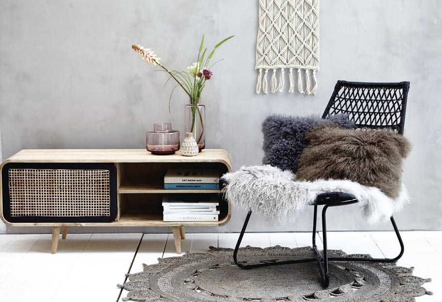 The Lene Bjerre Dea Media Cabinet next to a black rattan chair decorated with soft textiles. Image via Houseology.