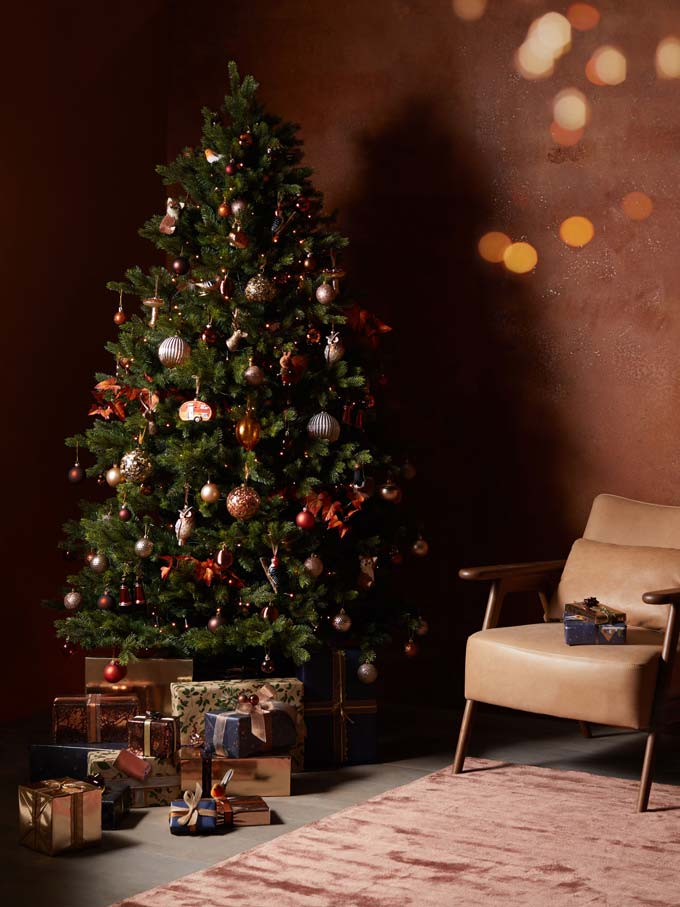 A green Christmas tree with deep rusty decorations - warm and inviting. Image via John Lewis & Partners.