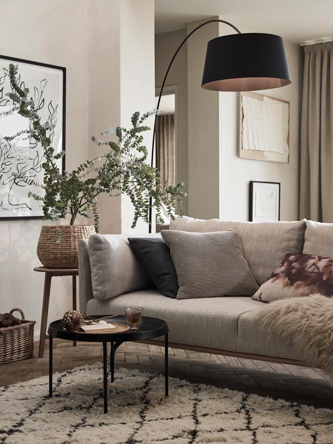 An impossibly chic Scandi-boho living room with an eclectic vibe and a neutral color palette and a few black accents like the floor lamp, the round coffee table and one of the decorative cushions on the sofa. Image by John Lewis.