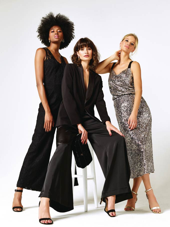 Three women in holiday season outfits. A black jumpsuit, a black satin pant-suit or a silver sequin maxi dress. Take a pick. Image via M&Co.