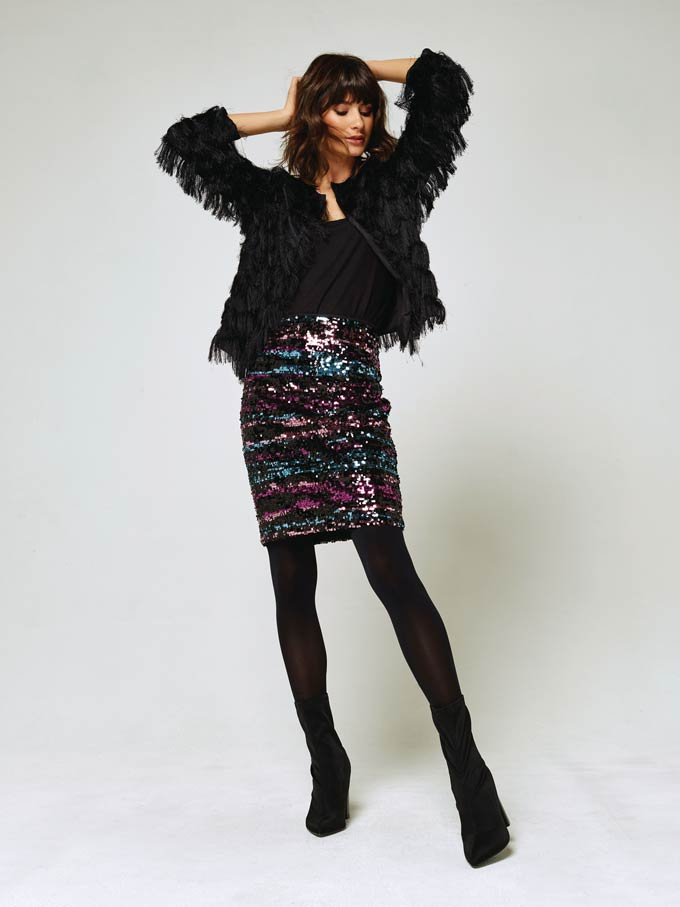 A festive outfit with a black layer jacket, black top, sequin striped skirt, black opaque tights and black ankle boots. Image via M&Co.