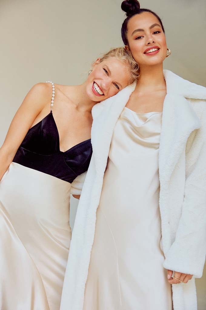 No rules against wearing white during the holiday season, right?! Two women dressed in off white dresses. On the left a color blocked black top white bottom dress. On the right, a cami looking creamy white dress under an off white faux fur. Image via Miss Selfridge.