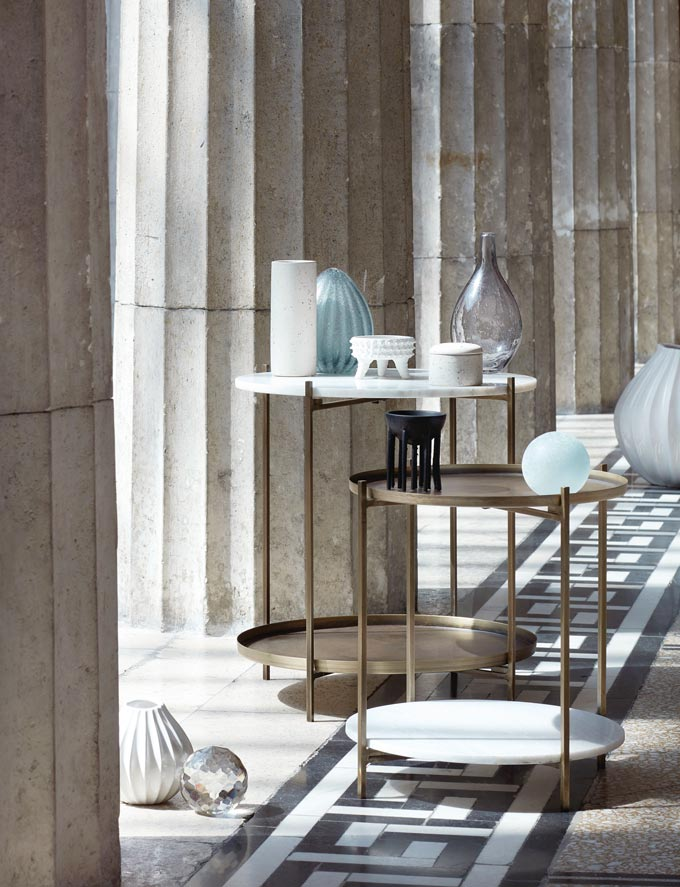 Two Broste Copenhagen Tristan side tables featuring marble and brass placed by some Roman marble columns. Image via Nest.co.uk.