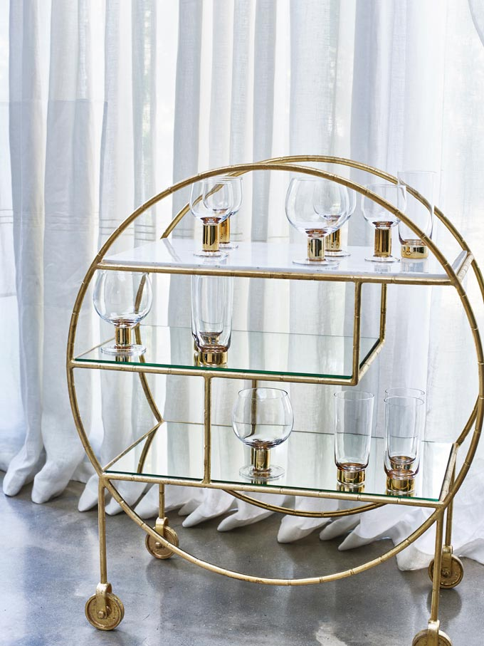 An art-deco inspired bar cart with a marble shelf from Oliver Bonas. Marble decor ideas.