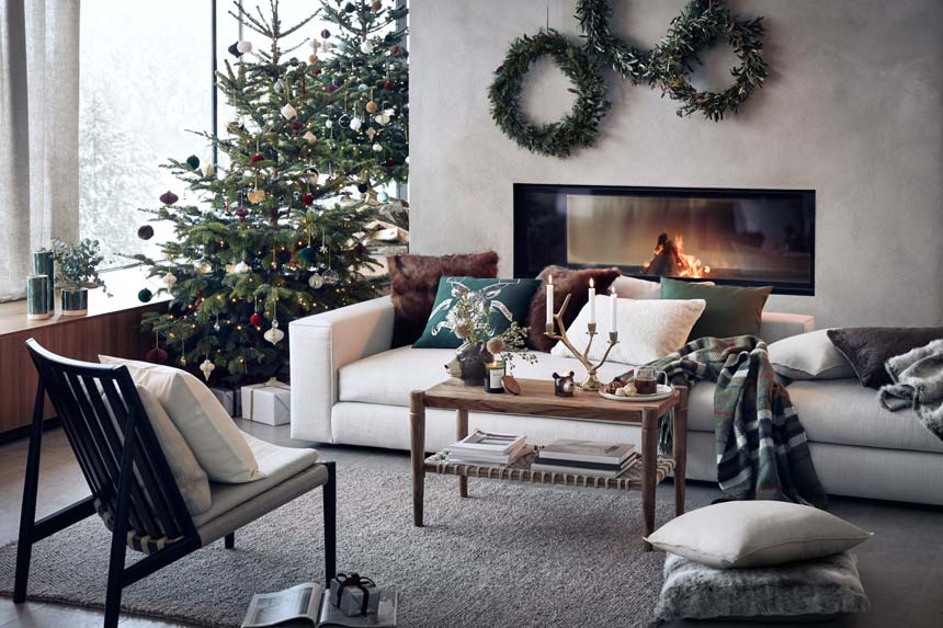 A beautiful contemporary living space with large windows, a Mid-century inspired armchair, an off white sofa in front of a modern fireplace and lots of Christmas decor on the coffee table and Christmas tree. Image via H&M homestores.