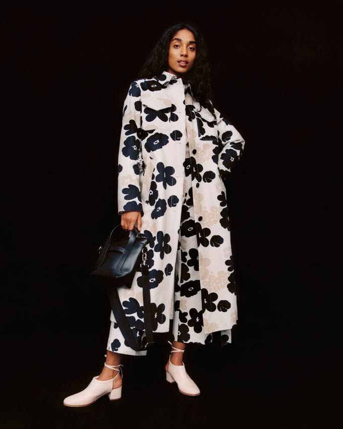 What a statement coat! A white overcoat with a black flower print paired with a black bag and white shoes. Image by Marimekko.