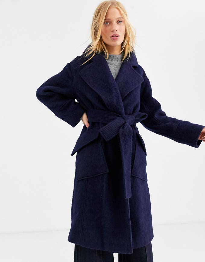 A blonde woman wearing a navy blue wool coat. Image via ASOS.