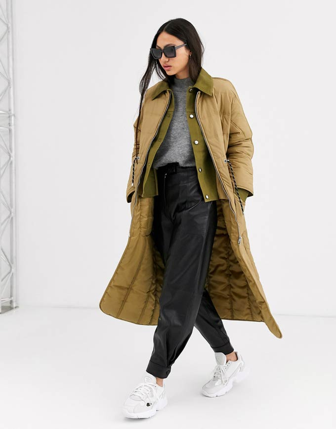 A mustard tone overcoat paired with a grey top, black faux leather wide leg pants, and white trainers. Image by ASOS.