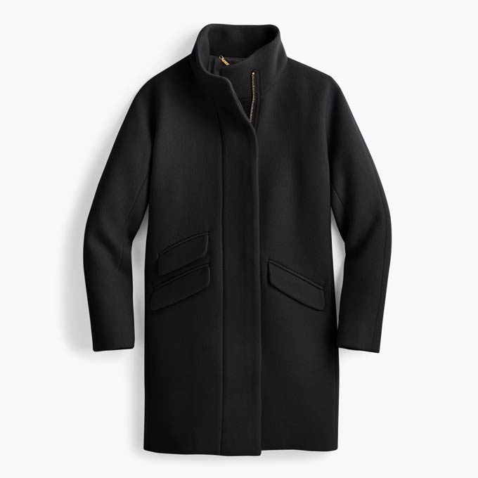 A flat lay of a black wool coat. Image via J.Crew.