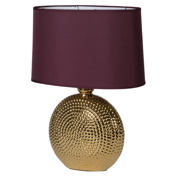 A hammered gold table lamp with a burgundy shade. By Audenza.