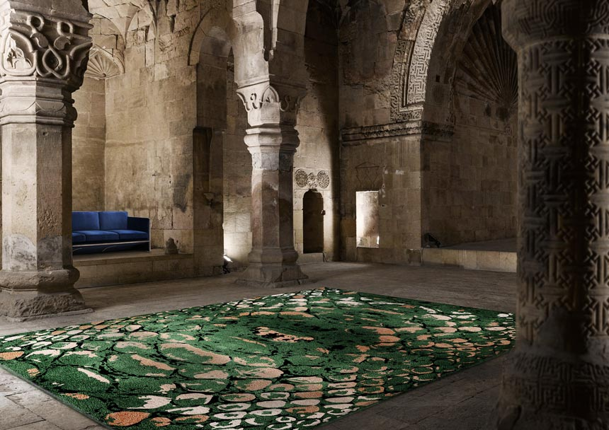Jaw dropping rug! The green reptile pattern rug lays in the middle of an old monument with a blue sofa in between a wall recess. Image via Rug'Society.