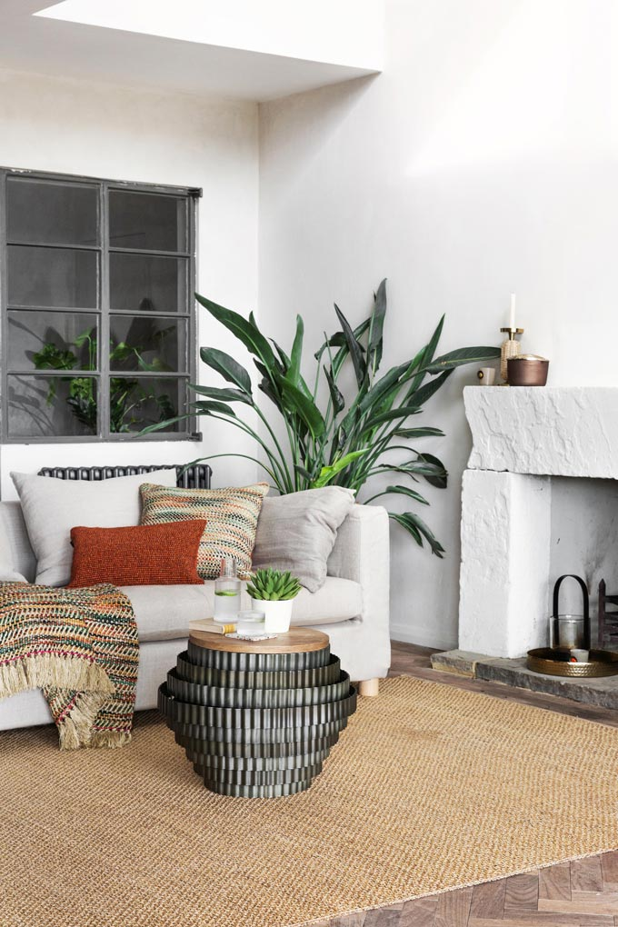 Green living continues to trend. A bright white living space with a white fireplace, a large plant next to it filling the gap between the white sofa and the fireplace. Image via Amara.