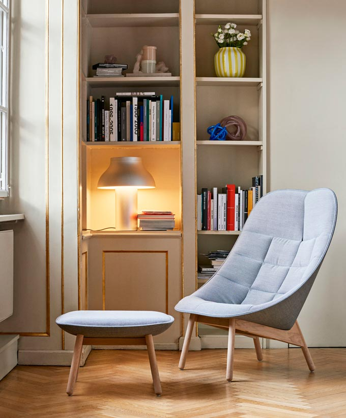 The Hay Uchiwa Lounge Chair and foot stool standing in front of a built-in bookcase with the Hay PC table lamp creating a cozy vignette. Image via Nest.co.uk.