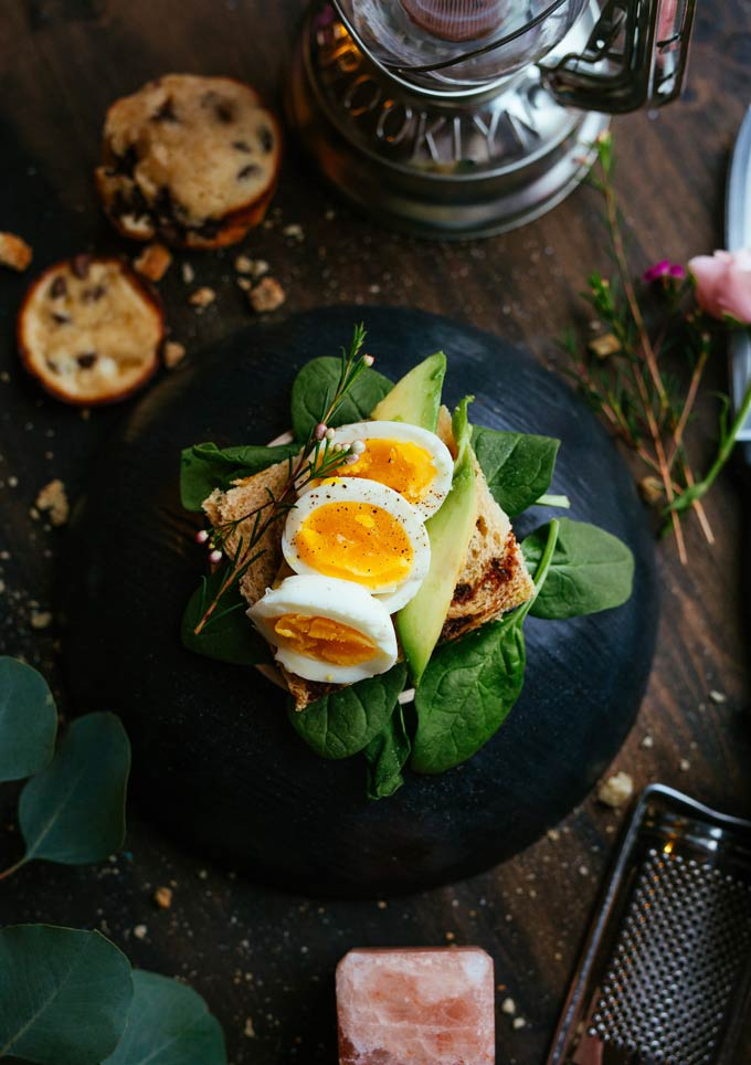 A beautifully styled sandwich with a hard boiled egg on top.