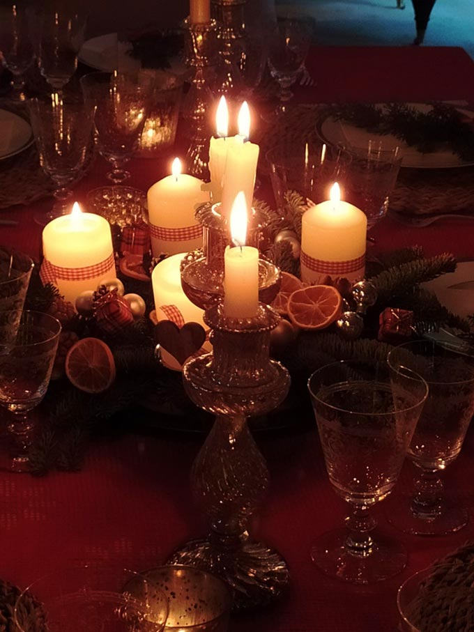 A close up view of an Advent wreath with its burning candles as the centerpiece on a Christmas table setting.