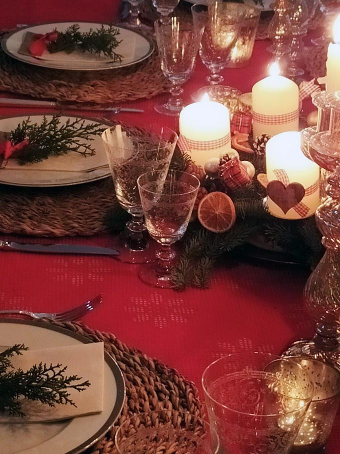Close up of a table setting for Christmas with an Advent wreath as the centerpiece.