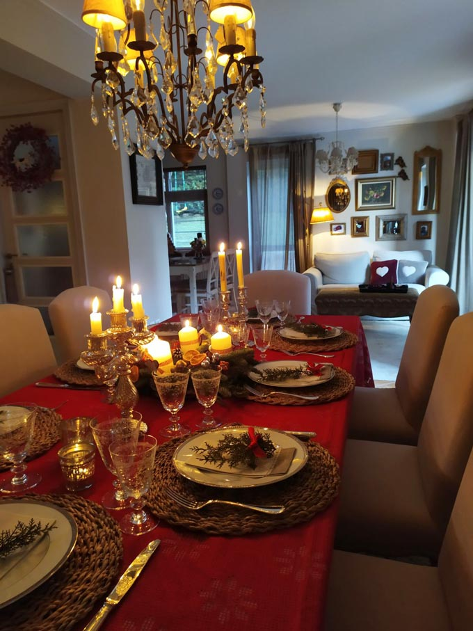 A beautifully styled dining table for Christmas with a red tablecloth and an Advent wreath. In the background there's a sofa with an art gallery wall.