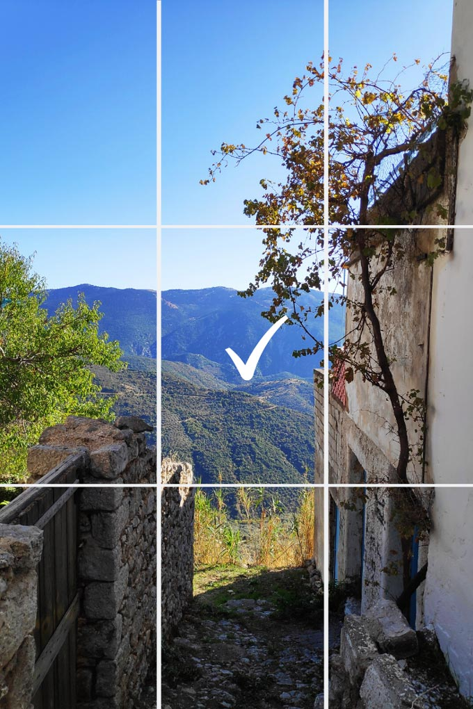 Looking from a passage at the blue green mountains in the background. Picture taken at Arachova, a villiage in Greece. A grid like overlay with a check mark in the middle pinpoints the center of the image.