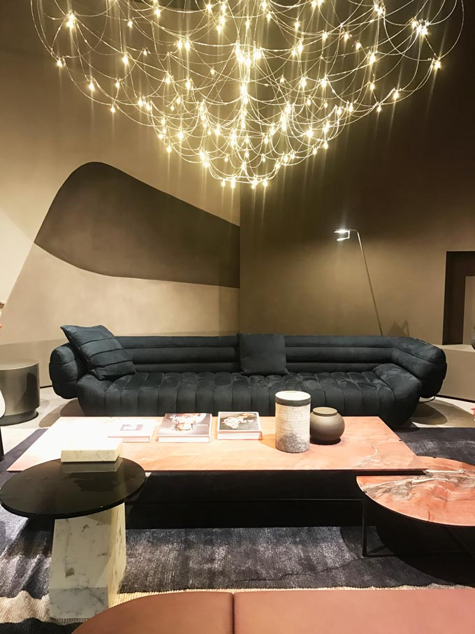 A contemporary installation with a dark grey sofa and pink marble coffee tables and a gorgeous huge delicate and modern chandelier as seen at Baxter.