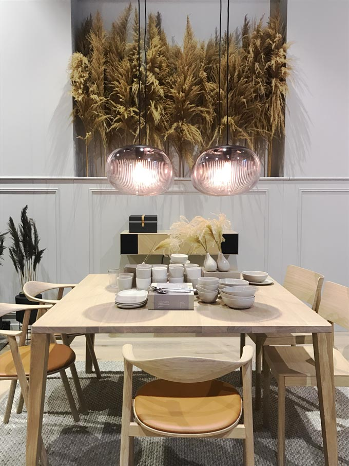 From Bolia. A dining set in light wood and two pendants lights. Pampas grass is used as decor in the background.