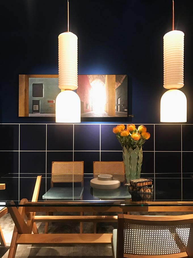 A dining set against a dark blue tiled wall with two pendant lights as seen at Cassina.