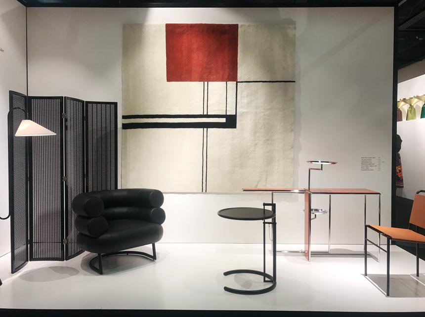 A booth at the imm Cologne 2020. A black divider, armchair, a wall tapestry and tables all part of this installation at Classicon.