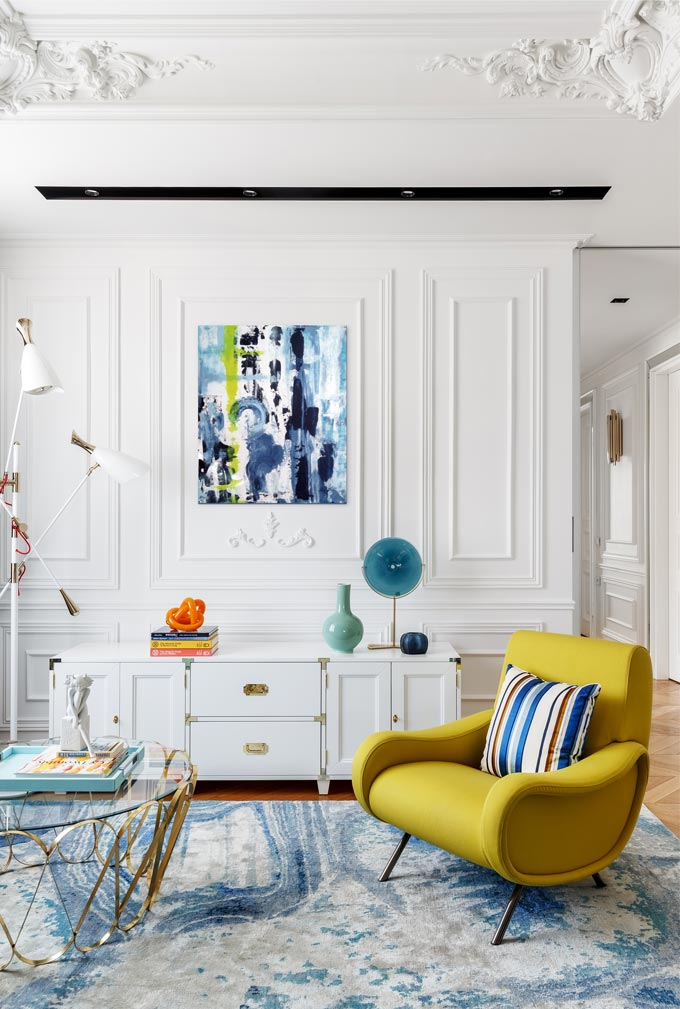 A colorful home interior. View of a striking mustard tone armchair in a white Parisian inspired living room designed by O2 Design Moscow studio. Image: Covet House/Sergey Krasyuk.