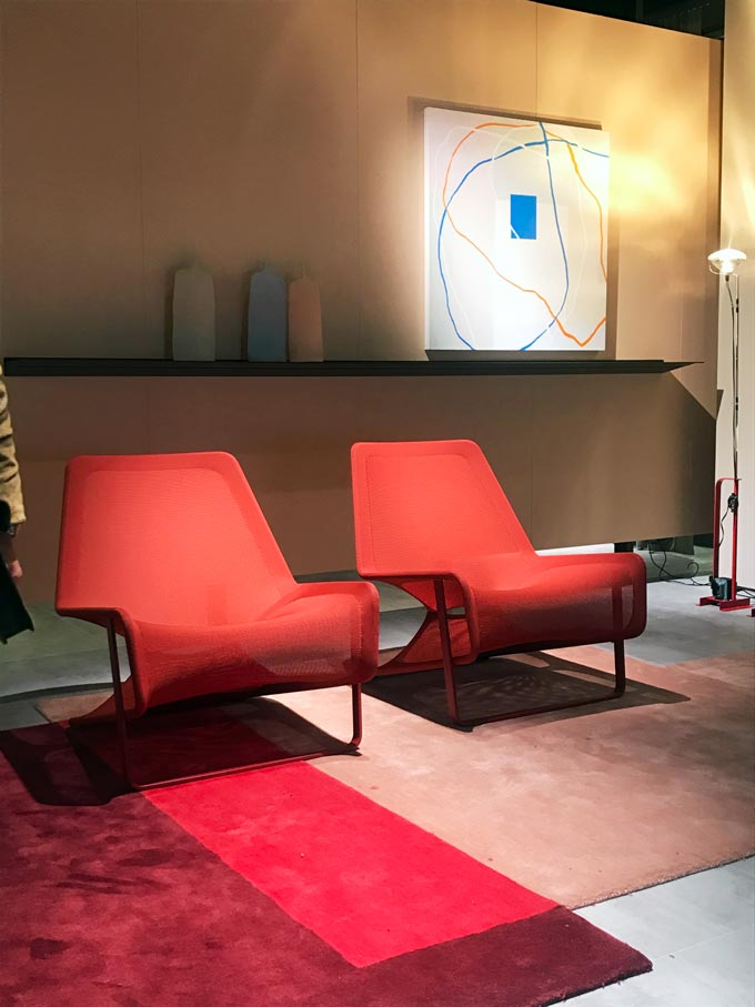 Two contemporary red armchairs side by side resting on a color blocked area rug.