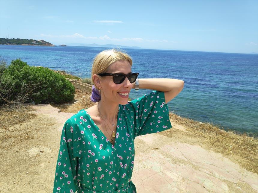 Elisabeth in a green playsuit near a coastline wearing shades.