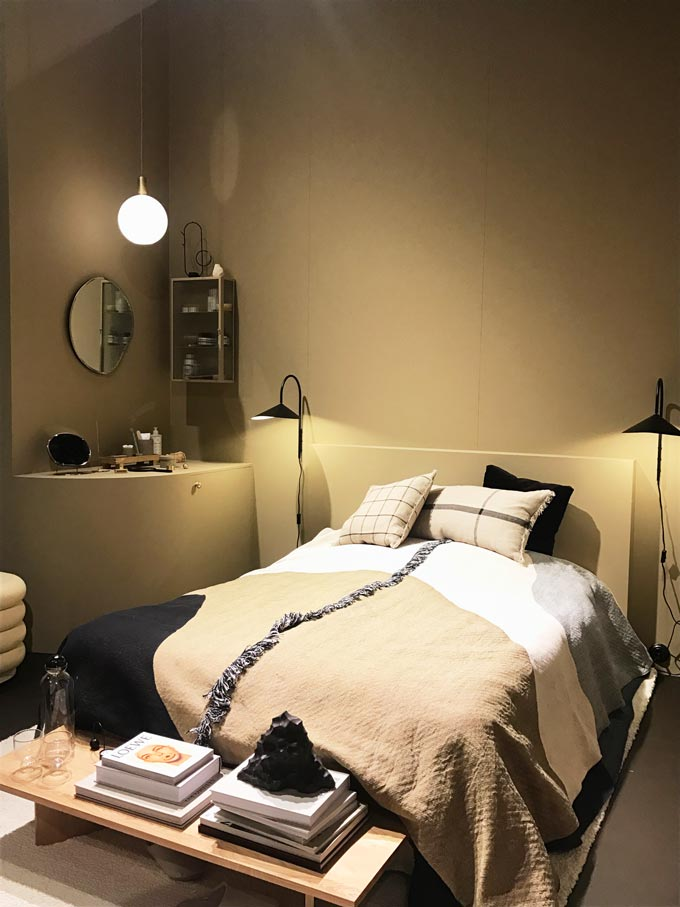 A contemporary bedroom setting with a tone-in-tone approach in an earthy light ochre hue as seen by Ferm Living.