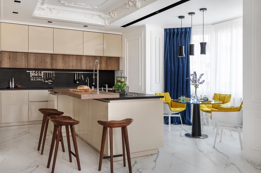 A contemporary kitchen in beige tones adjacent to a dining set featuring bright yellow armchairs in a luxurious apartment in Moscow. All part of a colorful home interior. Image: Covet House/Sergey Krasyuk.