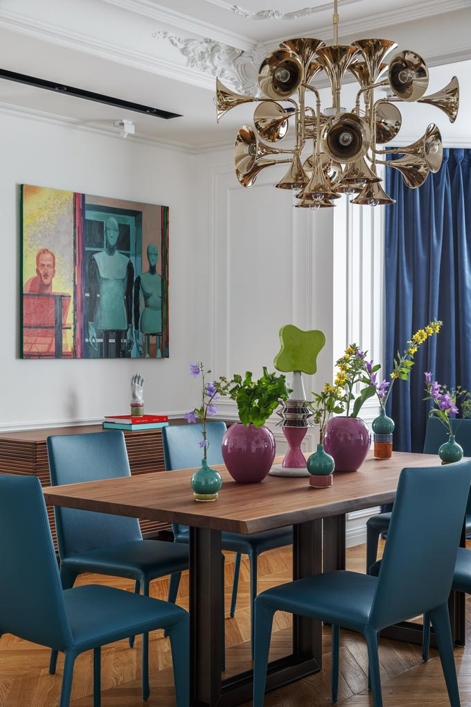 View of the dining space with its blue dining chairs, the eye-catching pendant chandelier and artwork on the wall. Image: Covet House/Sergey Krasyuk.